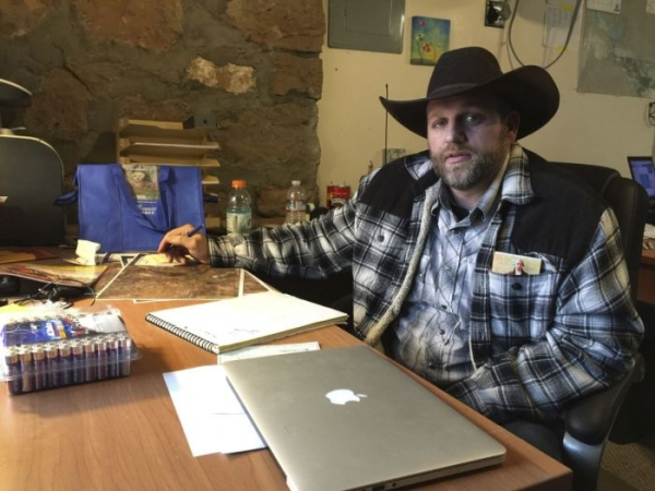 Ammon Bundy sits at a desk he's using at the Malheur National Wildlife Refuge in Oregon on Friday, Jan. 22, 2016. Bundy is the leader of an armed group occupying a national wildlife refuge to protest federal land policies. The leader of an armed group occupying the refuge met briefly with a federal agent Friday, but left because the agent wouldn't talk with him in front of the media.
